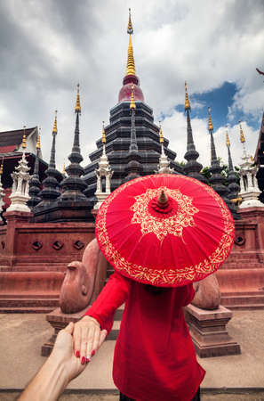 Woman with red traditional Thai umbrella holding man by hand and going to Black temple Wat Phan Tao in Chiang Mai, Thailand