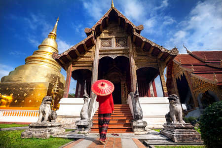 Woman tourist with red traditional Thai umbrella near Golden temple Wat Phra Singh in Chiang Mai, Thailand