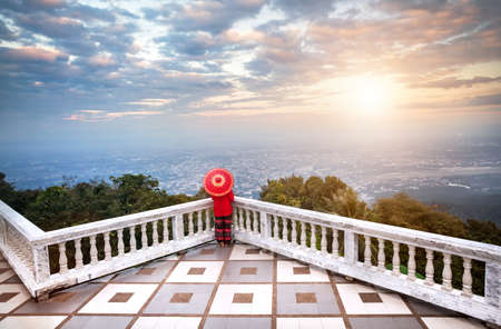 Woman with red Thai umbrella at view point looking at Chiang Mai city panorama at sunset in Thailand Stock Photo