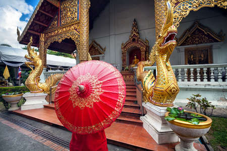 Woman tourist with red traditional Thai umbrella near Golden temple Wat Phra Singh with Big Dragon statues in Chiang Mai, Thailand Stock Photo