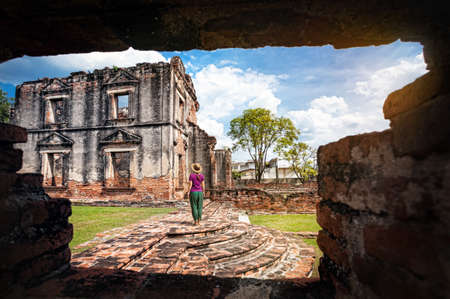 asian art: Woman in hat looking at ancient ruined Temple of city Lopburi, Thailand Stock Photo
