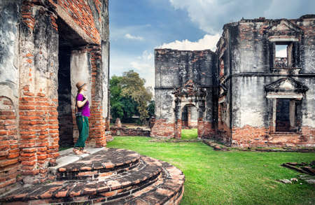 Woman tourist with photo camera looking at ancient ruined Temple of city Lopburi, Thailand Stock Photo
