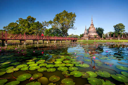 Tourist Woman in red costume on the bridge looking at ancient Stupa in Wat Sa Si  near the pond with lotus in Sukhothai Historical Park, Thailand