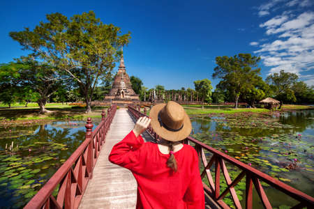Tourist Woman in red costume looking at ancient Stupa in Wat Sa Si of Sukhothai Historical Park, Thailand