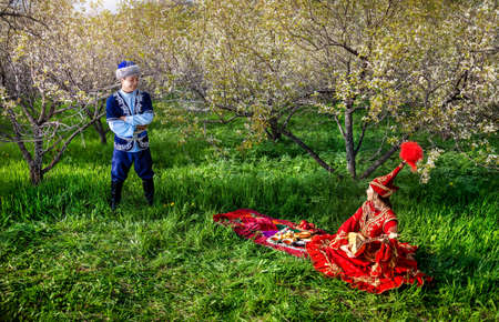 Couple in Kazakh costume in Spring Blooming apple garden at picnic with dombra in Almaty, Kazakhstan, Central Asia