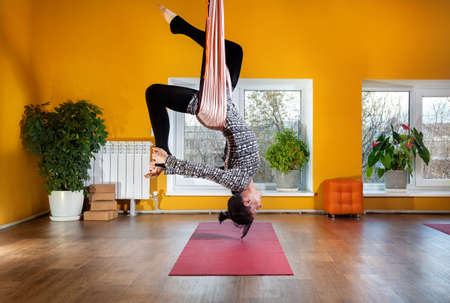 Young woman doing antigravity yoga inverted position at wellness studio with yellow walls