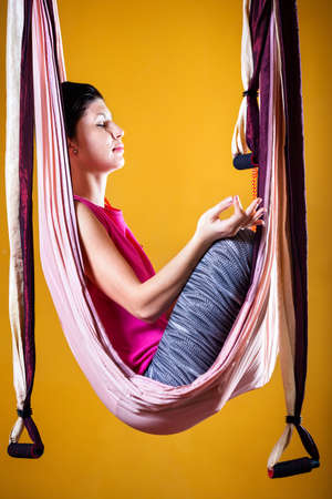 dhyana: Young woman doing antigravity yoga meditative position at studio with yellow walls