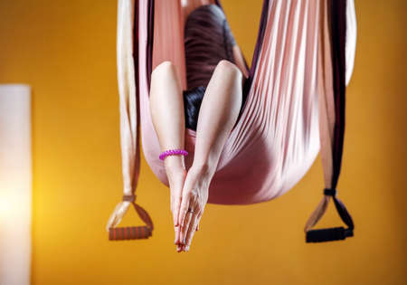 yellow walls: Young woman doing antigravity yoga meditative position in hammock at studio with yellow walls
