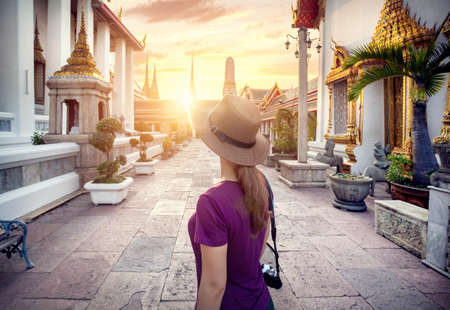 wat pho: Tourist woman in the hat and purple t-shirt with photo camera in Wat Pho temple at sunset in Bangkok, Thailand Stock Photo