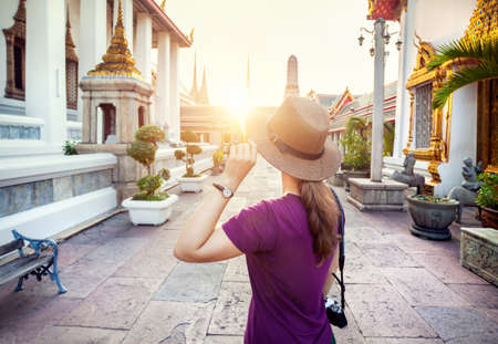 Tourist woman in the hat and purple t-shirt with camera in Wat Pho temple at sunset in Bangkok, Thailand