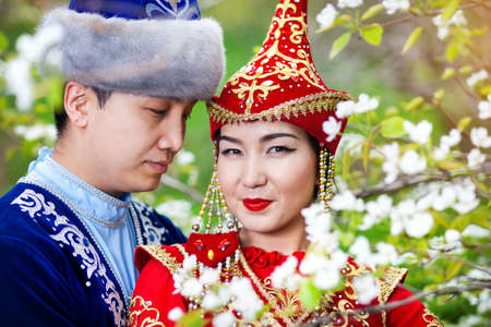 Portrait of Happy couple in Kazakh costumes in Spring Blooming apple garden of Almaty, Kazakhstan, Central Asia