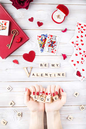 white red: MOSCOW, RUSSIA – FEBRURARY 19, 2017: Illustrative editorial image of Valentines Day romantic concept. Woman with red nails holding Love word from wooden letters flat lay Editorial