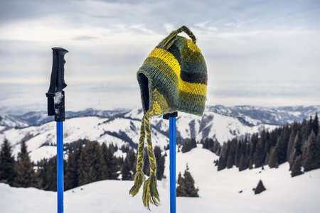Handmade hat from green wool on the trekking pole in the mountains. Tracking concept. Stock Photo