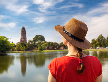 Tourist Woman in red t-shirt and hat looking at ancient temple in South East Asia
