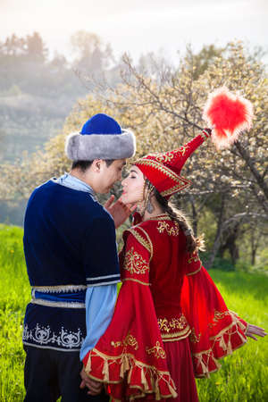 Couple in Kazakh ethnic costume kissing in Spring Blooming apple garden of Almaty at beautiful sunset, Kazakhstan