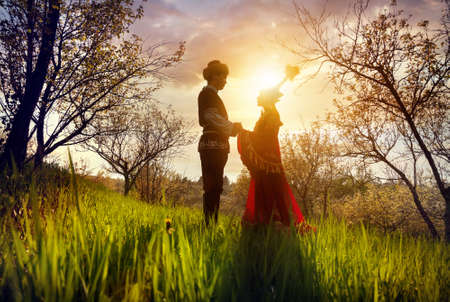 siluet: Couple in Kazakh ethnic costume in silhouette in Spring Blooming apple garden at beautiful sunset