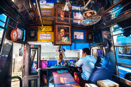 CHIANG RAI, Thailand - November 26, 2016: Cabin of public bus with portrait of King and driver waiting of departure at the station terminal