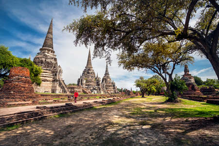 Tourist Woman in red costume walking near ancient ruined stupa in Ayutthaya Historical Park, Thailand
