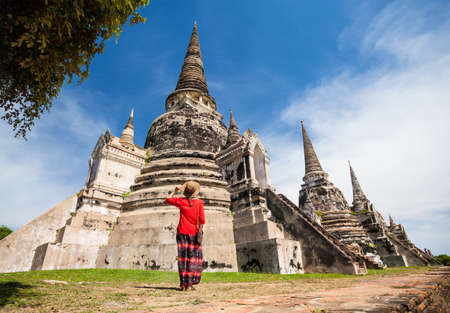 Tourist Woman in red costume looking at ancient ruined stupa in Ayutthaya Historical Park, Thailand