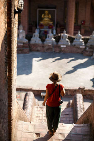 siluet: Tourist Woman in hat and photo camera in ancient Buddhist complex in Ayutthaya Historical Park, Thailand