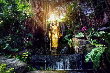 Golden Buddha statue in the tropical garden with waterfall in Wat Saket Golden Mountain Temple in Bangkok
