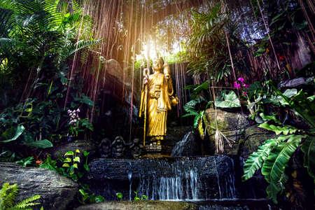 Gouden Boeddhabeeld in de tropische tuin met waterval in Wat Saket Golden Mountain Temple in Bangkok