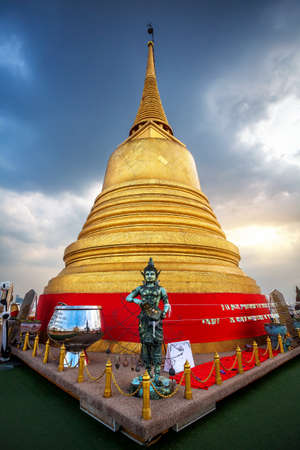 Big golden Stupa at blue cloudy sky on the roof of Wat Saket temple in Bangkok, Thailand