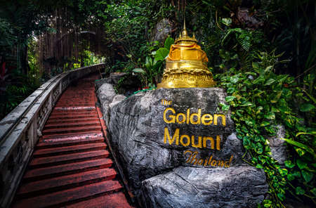 Golden Stupa statue in the tropical jungle near the stairs in Wat Saket Golden Mountain Temple in Bangkok