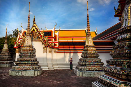 Woman tourist near Ancient Royal Stupas and pagoda in Wat Pho temple in Bangkok at sunset