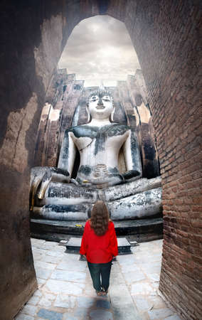 Woman in red shirt standing near giant statue of Buddha call Phra Achana in Wat Si Chum in Sukhothai Historical Park, Thailand