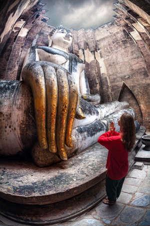巨大な像、仏の近くに立っている赤いシャツの女性は、スコータイ歴史公園、タイのワットシーサチュムで Phra Achana を呼び出す