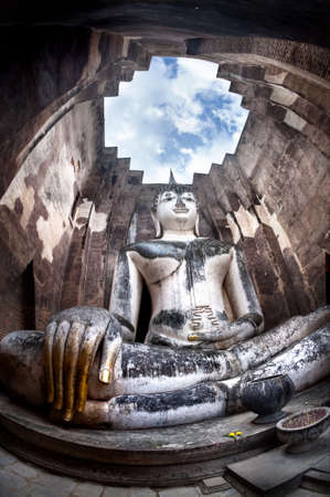Giant statue of Buddha call Phra Achana in Wat Si Chum at Grey overcast sky in Sukhothai Historical Park, Thailand