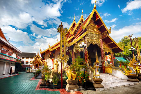 Golden Pagoda with dragon in Buddhist monastery of Chiang Rai, Thailand Stock Photo