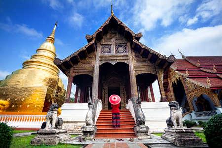 Toerist van de vrouw met rode traditionele Thaise paraplu in de buurt van Golden tempel Wat Phra Singh in Chiang Mai, Thailand