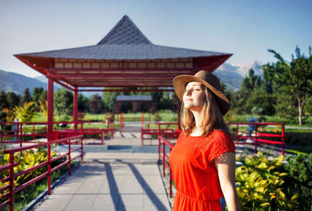 Portrait of beautiful woman in orange dress and hat near the pagoda in Japanese Garden