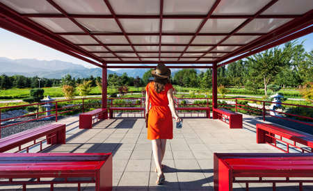 Woman in orange dress with photo camera going to the Japanese Pagoda Stock Photo