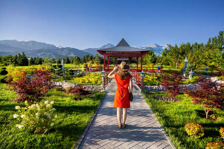 Woman in orange dress with hat looking at the Japanese Pagoda garden