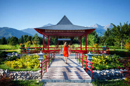 Woman in orange dress with hat going to the Japanese Pagoda garden Stock Photo