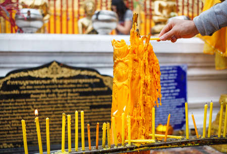 Hand with candle in Wat Doi Suthep Buddhist Temple in Ciang Mai, Thailand Stock Photo