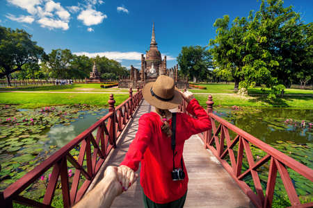 Tourist Woman in red shirt holding her husband by hand and going to ancient stupa in Sukhohai Historical Park, Thailand