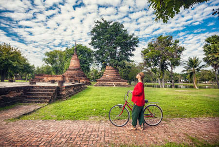 Woman in red shirt with bicycle looking at old ruined Buddhist temple in Sukhothai historical park, Thailand