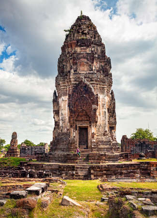 Woman in hat looking at ancient ruined Temple of city Lopburi, Thailand Stock Photo