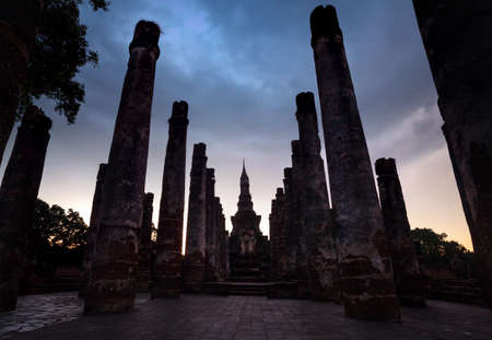 Ancient ruined column of Temple in Sukhothai at overcast sunset sky, Thailand