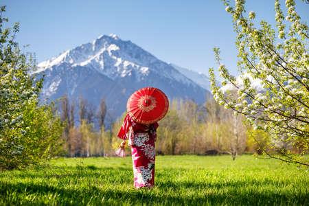 山を背景に桜の花と庭で赤い傘と着物姿の女性