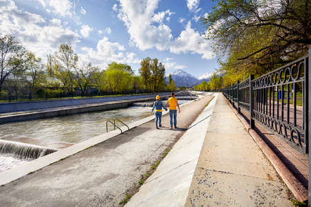 Happy couple in blue and yellow costumes walking down the river near snowy mountains in Almaty, Kazakhstan photo