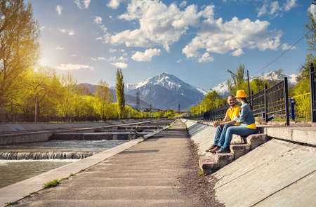 Happy couple in blue and yellow costumes sitting on the stairs near the river and snowy mountains background in Almaty, Kazakhstan photo