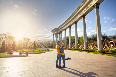Happy couple in blue and yellow cloths hugging near column and bridge in famous park in Almaty, Kazakhstan photo