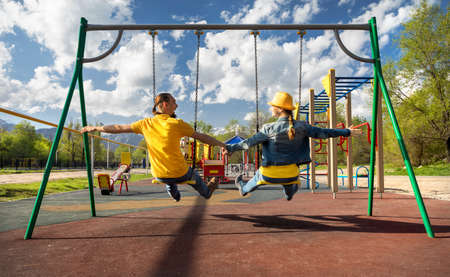 Happy couple in blue and yellow clothes rides at swing in children park in Almaty, Kazakhstan photo