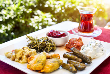 Turkish tea and meze vegetarian starter in restaurant in traditional glass on the red table in Turkey Stock Photo