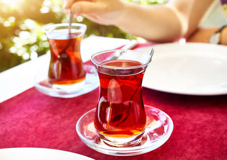 Turkish tea in traditional glass in restaurant on the red table in Turkey